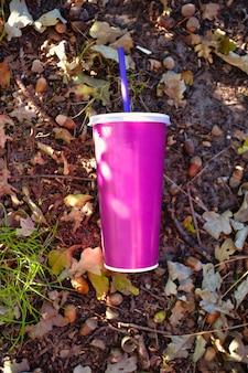 挽いたソーダ紙の森に投げられたプラスチック製の蓋とストローが付いた紙のソフトドリンクカップ
