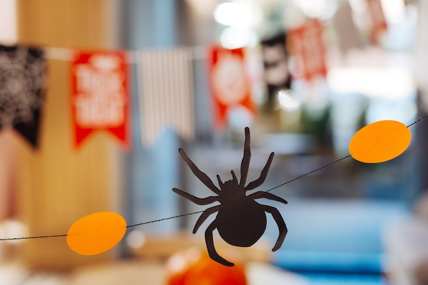 Paper spider. close up of little scary paper spider lying between orange decorations for amazing halloween party