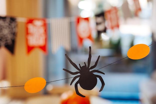 紙蜘蛛。素晴らしいハロウィーンパーティーのためのオレンジ色の装飾の間に横たわっている小さな怖い紙のクモのクローズアップ