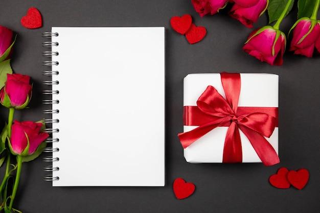 Макет бумажного спирального блокнота и подарочные коробки с красной лентой, сердечками, розами на темной поверхности