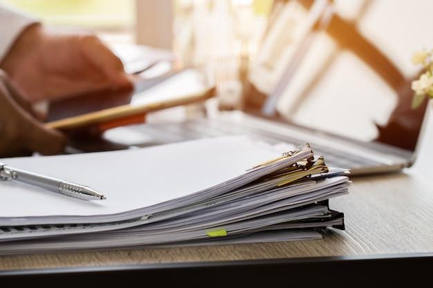 用紙の束、事務机の上の未完成の書類の山