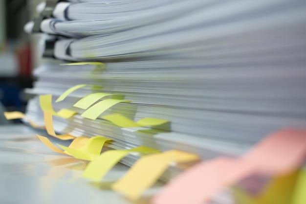 ペーパースタック、ビジネス機能に関連するオフィスデスク上に投稿された未完成の文書の束