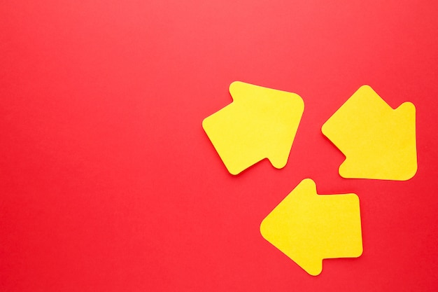 Paper sticky notes in shape of arrow on red background
