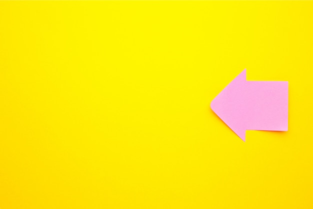 Paper sticky notes in shape of arrow on yellow background