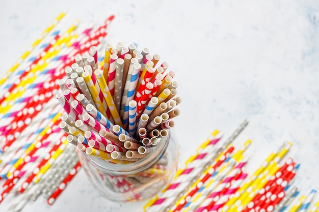 Paper straws of different colors on light background with copy space