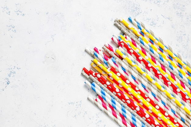 Paper straws of different colors on light tablewith
