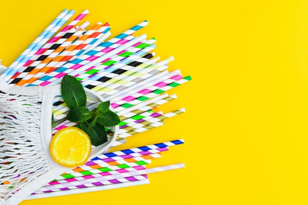 Paper straws of different colors on yellow background and bach with a lemon and leaves