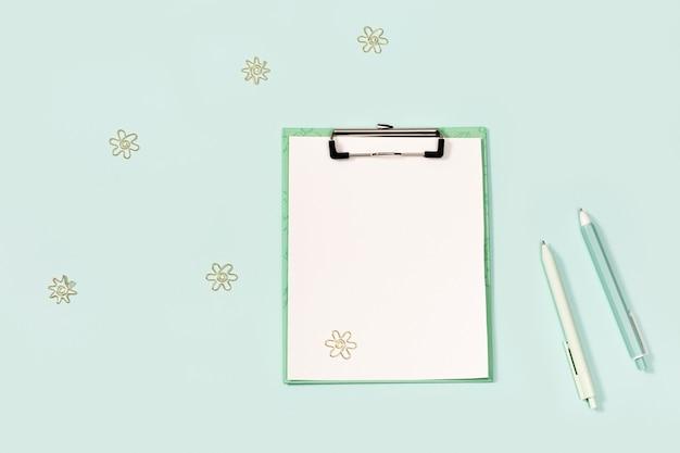 クリップと文房具付きの紙タブレット。学校のコンセプトに戻ります。青と白の色のペン、そして現代のペーパークリップ。上から見て、モックアップします。