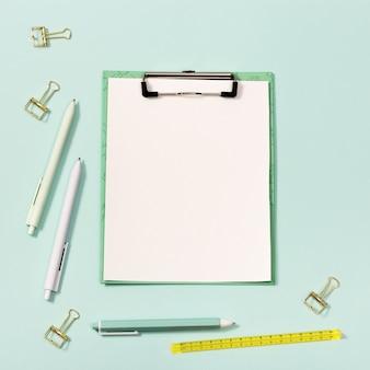 Бумажный планшет с зажимом и канцелярскими принадлежностями вернуться в школу концепции