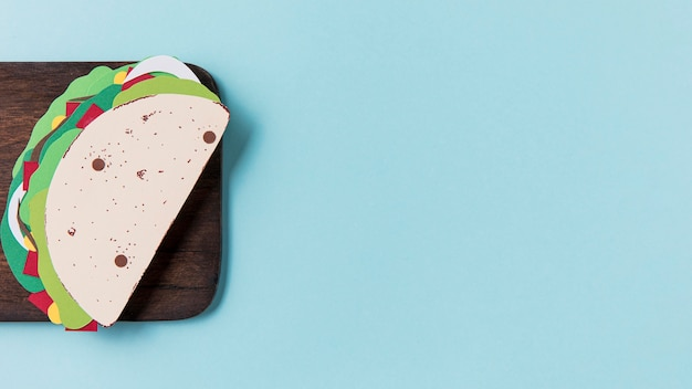 Paper taco on wooden board flat lay