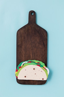 Paper taco on wooden board top view