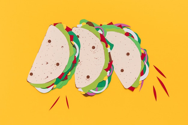 Paper tacos on yellow background top view