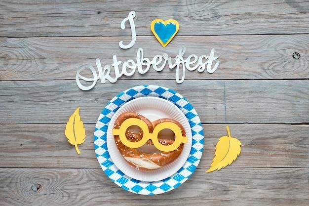 Текст с надписью «я люблю октоберфест», плоско лежал на деревенском деревянном столе с забавным кренделем