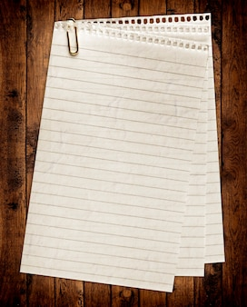 Paper textured notebook.page isolated on the wood backgrounds.