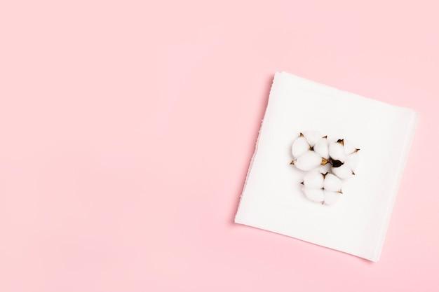 ピンクの空間にペーパータオルと綿の花。コンセプトは100%ナチュラルな商品で、繊細でソフトです。フラット横たわっていた、トップビュー。バナー