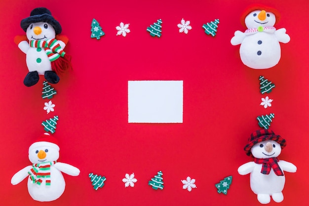 Paper between toy snowmen and christmas decorations