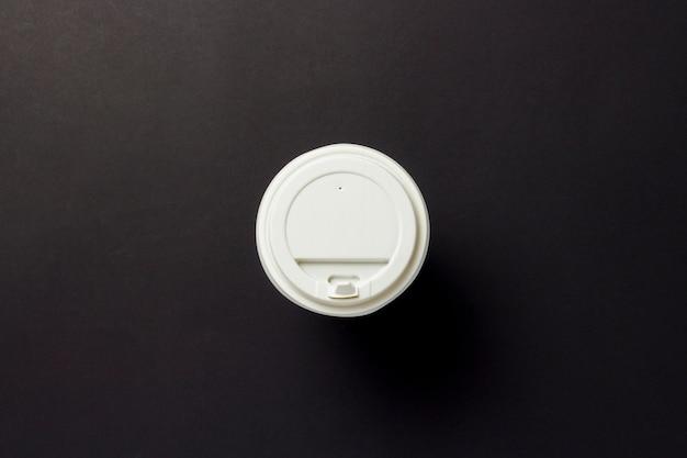 Бумажный трансферный стаканчик с пластиковой крышкой, кофе или чай на черном фоне. концепция завтрак, фаст-фуд, кафе, пекарня, обед. плоская планировка, вид сверху.