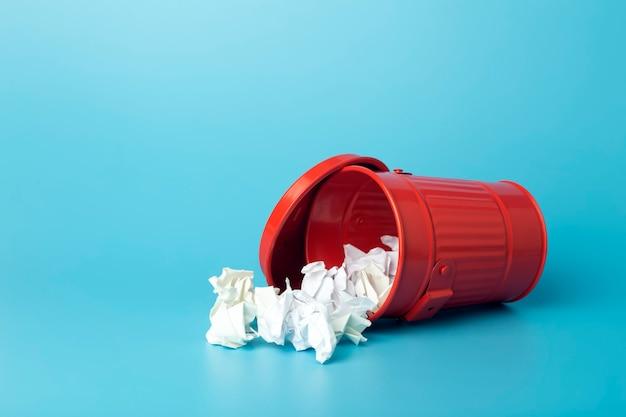Мусор и отходы бумаги в мусорном ведре на синем фоне. концепция сортировки и переработки отходов и бумаги