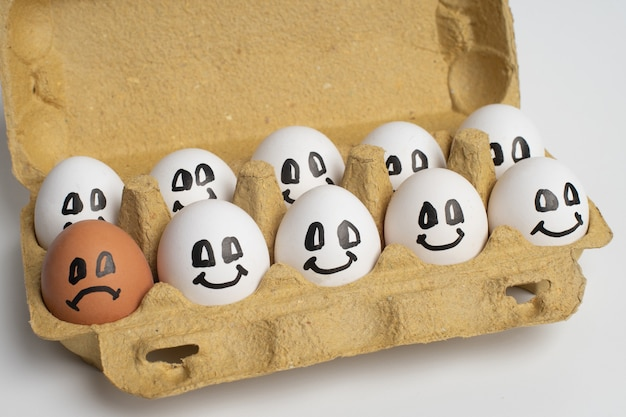 Paper tray full of smile white eggs and only one different sad orange egg.