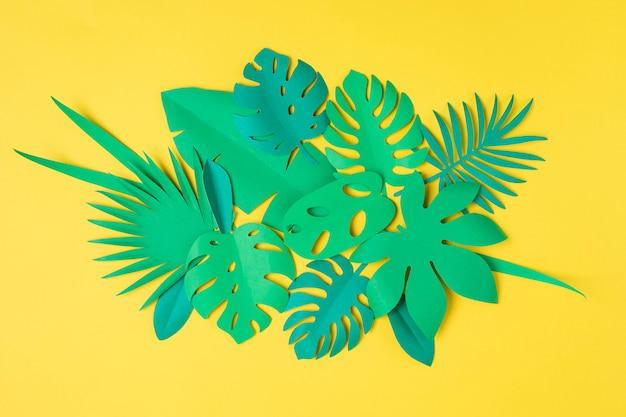 黄色のパステルカラーの背景に熱帯の葉を紙