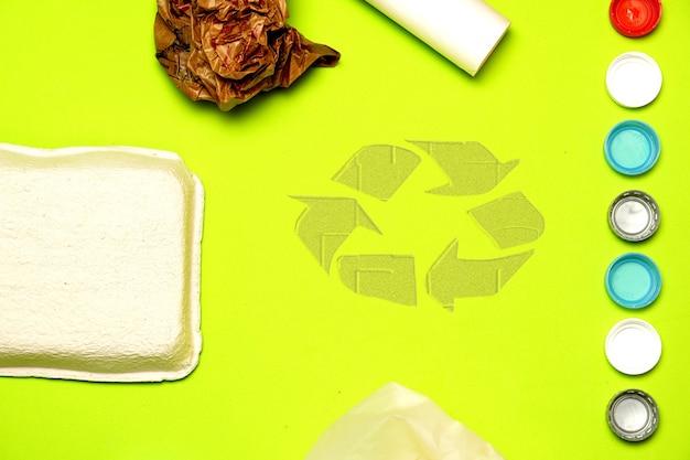 リサイクルシンボルの横にある緑の背景に紙のチューブボックスとビニール袋。リサイクルコンセプト。フラットレイフラットデザイン
