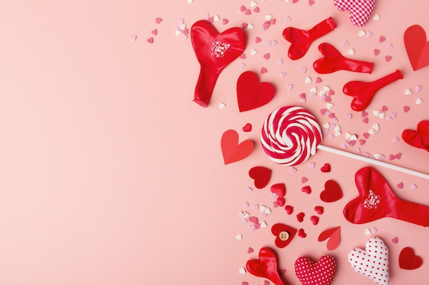Paper valentines day hearts with sweets on pink