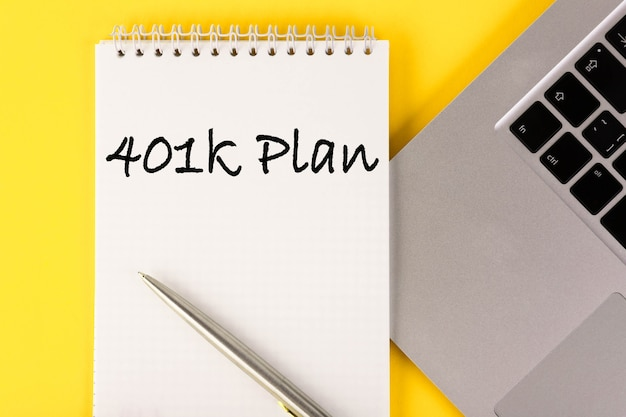 노란색 벽에 노트북이있는 테이블에 401k 계획이있는 종이.