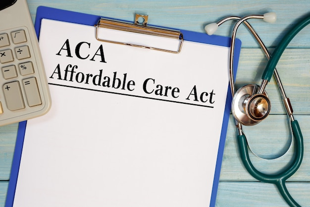 Paper with aca affardable care act on the office table