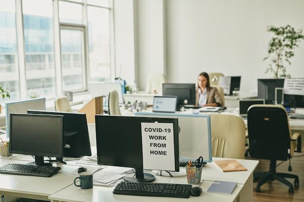 Бумага с объявлением о работе из дома на одном из компьютерных мониторов в офисе с занятым секретарем, работающим на заднем плане
