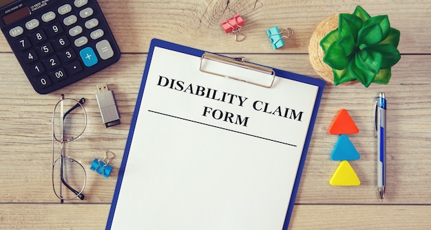Paper with disability claim form on office wooden table with calculator, plant and office supplies