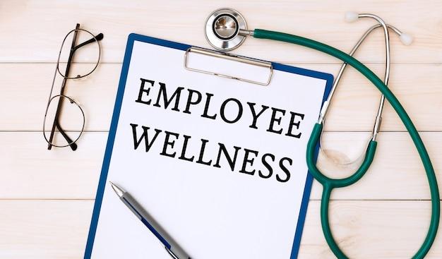 オフィスの机、聴診器、眼鏡に従業員の健康と紙