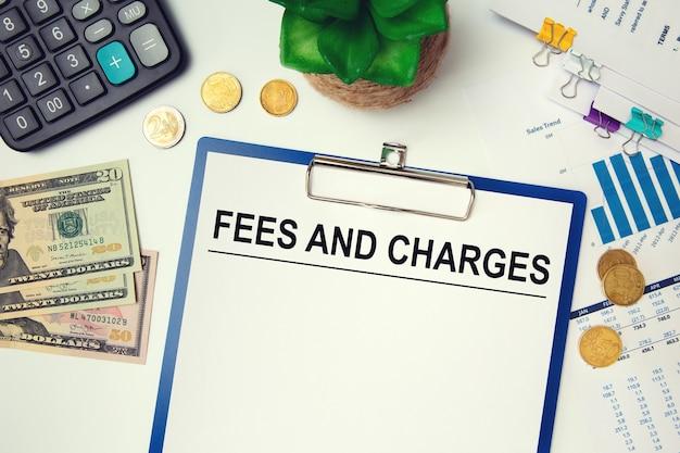 オフィスのテーブル、電卓、お金に手数料と料金が記載された紙