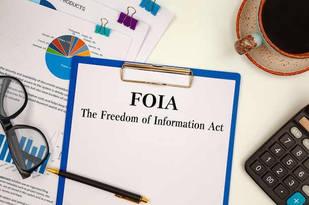 Paper with the freedom of information act foia on the table, calculator and glasses