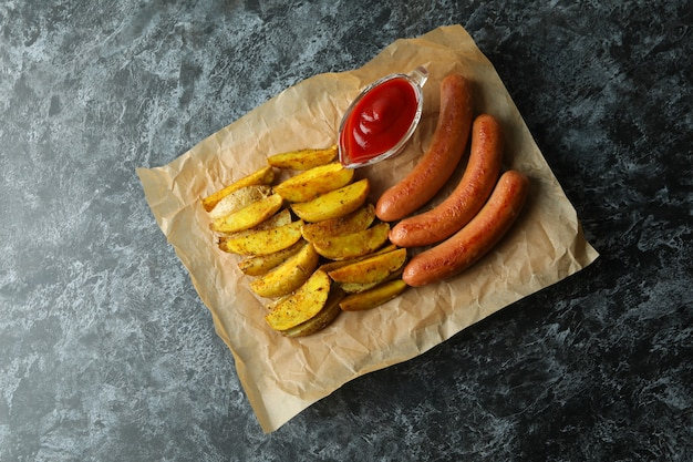 Paper with fried potato, sauce and sausages on black smokey background