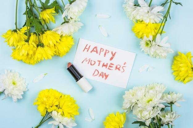 口紅と新鮮な花の束の近くの幸せな母の日の言葉と紙