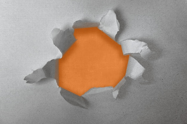 Paper with a hole torn in the middle with colored background