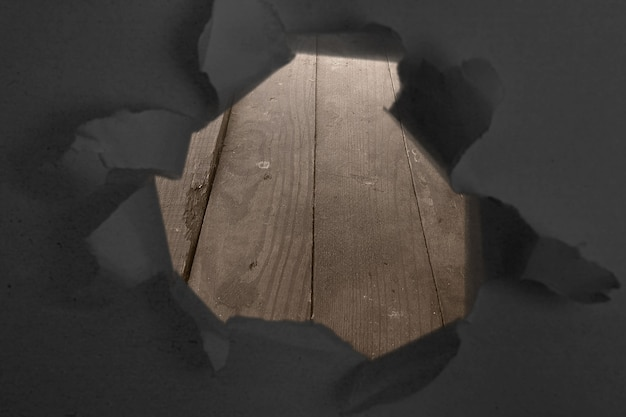 Paper with a hole torn in the middle with wooden table background