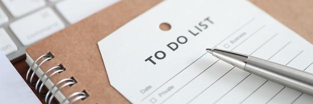 ノートブックのクローズアップアクション計画の概念に横たわっているリストを行うための碑文と紙