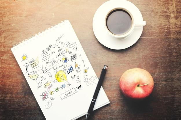 木製のテーブルにペン、コーヒーカップ、赤いリンゴと紙