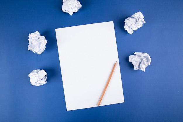 파란색 표면에 연필과 종이 뭉치와 종이