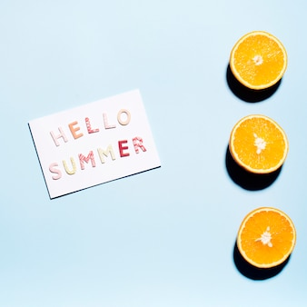 Paper with text hello summer with juicy oranges halves