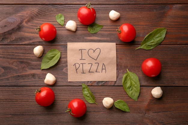 Paper with text i love pizza and ingredients on wooden table