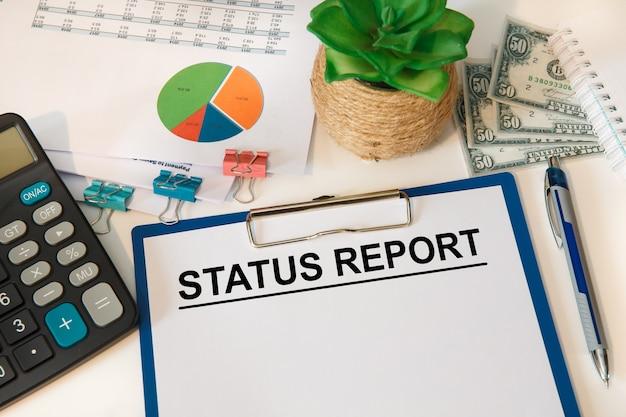 사무실 테이블, 계산기 및 돈에 텍스트 상태 보고서가있는 용지