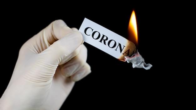 Бумага с текстом коронавирус горит в руке. концепция прекращения пандемии коронавируса.