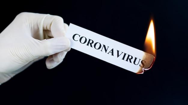 Бумага с текстом коронавирус горит в руке. концепция конца пандемии коронавируса. вирус побежден.