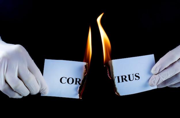 Бумага с текстом коронавирус горит на черном фоне. концепция победы в борьбе с вирусом.