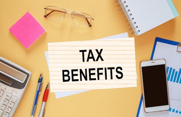 편지지 가운데 사무실 테이블에 tax benefits라는 텍스트가있는 종이.