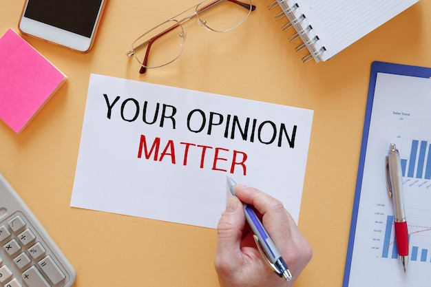 편지지 가운데 사무실 테이블에 your opinion matter라는 텍스트가있는 종이.