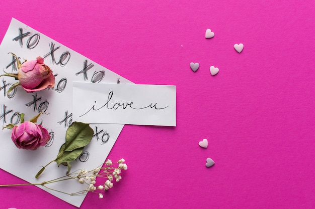 Paper with title near ornament hearts and set of flowers