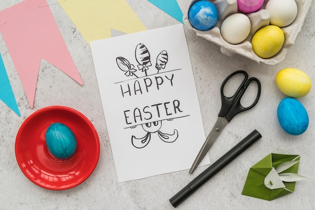 Paper with title near set of easter eggs, scissors and origami of rabbit